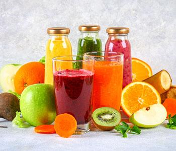 bicchieri e bottiglie di vetro con succhi di frutta diversi gusti e colori
