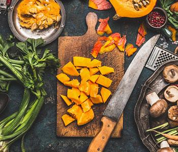 zucca tagliata a pezzi sul tagliere con foglie e altri ingredienti intorno