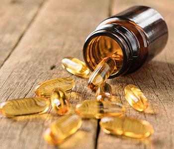 capsule softgel gialle che escono dal vaso sul tavolo di legno