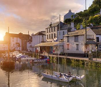 lago con piccole barche e case attorno con tramonto