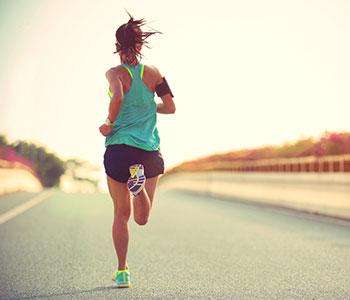 donna che corre con vestiti da ginnastica su strada deserta