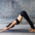 donna in palestra che fa la posizione di yoga conosciuta come downwardfacing dog