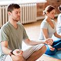 Uomo e donna che si siedono a gambe incrociate facendo meditazione