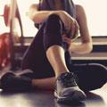donna seduta in palestra con abiti da ginnastica che fa allenamento