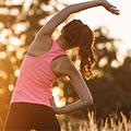 una donna in abiti allenamento che fa stretching al tramonto