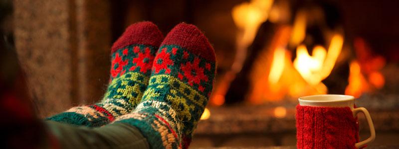 donna con calze di Natale accanto al fuoco con una tazza di tè