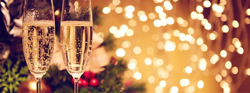 due bicchieri di champagne davanti alle luci di Natale