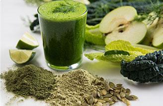 bicchiere di frullato verde di spirulina in mezzo a polvere chicchi e verdura