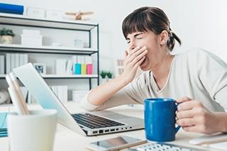 donna seduta al computer che sbadiglia mentre è davanti al pc
