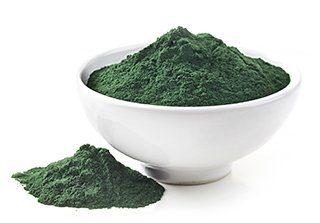 ciotola bianca con polvere di spirulina verde su sfondo bianco