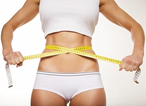 corpo di donna in abiti da palestra bianchi che si misura la circonferenza con un metro