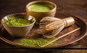 Vassoio con piccole ciotole di argilla riempite con polvere di matcha verde chiaro