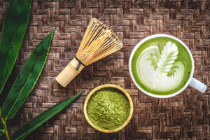 Ciotolina riempita con polvere di matcha e una tazza di tè verde matcha