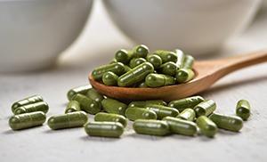 capsule verdi di moringa su cucchiaio di legno marrone