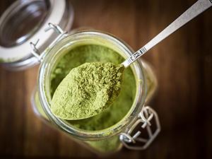polvere di moringa verde in tazza di vetro su tavolo marrone