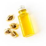 olio giallo in boccetta di vetro con semi accanto su sfondo bianco