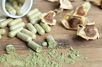 capsule verdi di moringa con polvere verde che esce su un tavolo marrone