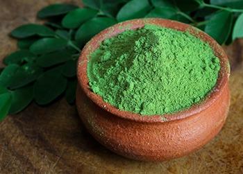 polvere verde di moringa in una ciotola e foglie di moringa spezzettate