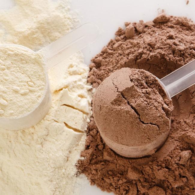 due misurini pieni di proteine in polvere gusto vaniglia e cioccolato
