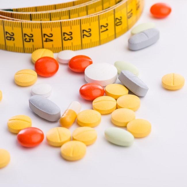 selezione di pastiglie per dimagrire con metro a nastro