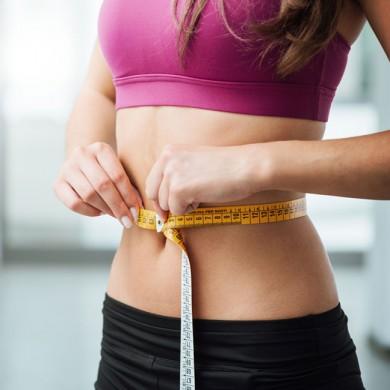 giovane ragazza in forma misura la vita con un metro a nastro