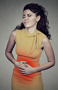 donna in abito giallo che si tocca la pancia gonfia