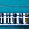 diverse lattine di metallo con spezie a stella su una mensola contro una pietra blu