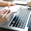 una persona che scrive su un quaderno mentre è seduto davanti al computer