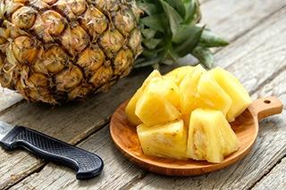 ananas tagliato a cubetti vicino a frutto ananas su tavola