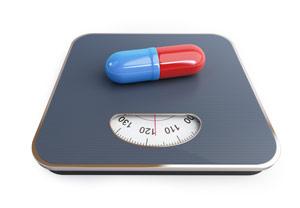 fotografia di una bilancia con sopra una pillola blue e rossa