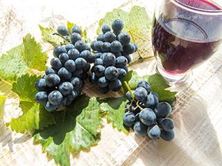 grappoli di uva nera e foglie di vite su tavola marrone