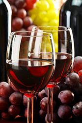 bicchieri di vino rosso e uva rossa nello sfondo su tavolo marrone
