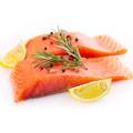 Salmone con spicchi di limone e foglie di rosmarino su uno sfondo bianco