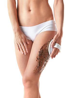 scrub anticellulite applicato sulle gambe e cosce e massaggiato con apparecchio contro cellulite