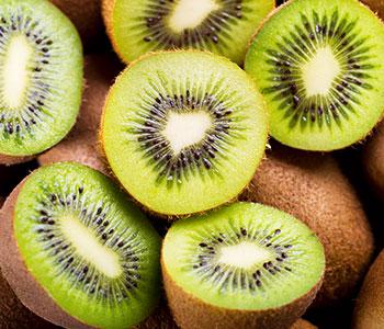 kiwi verdi tagliati a metà su kiwi interi marroni visti dall'alto