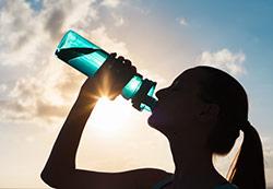 donna all'orizzonte che beve acqua detox da bottiglia