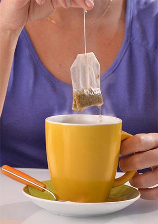 infuso in tazza gialla e bustina di te che viene estratta