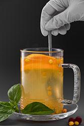 inufos arancione in tazza di vetro con foglie verdi a lato