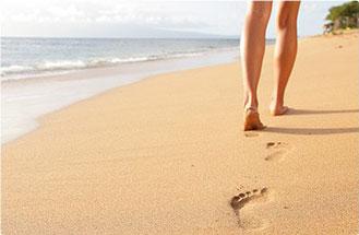 donna che cammina sulla spiaggia con segni di piedi sulla sabbia