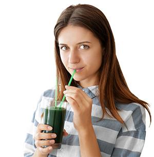 ragazza che beve un frullato verde a base di spirulina