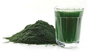 bicchiere con frullato a base di spirulina e polvere verde di spirulina