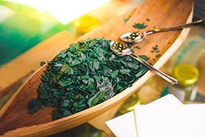 foglie di alga spirulina spezzettate su barca di legno