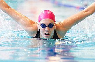 donna che nuota a delfino con cuffia rosa in piscina