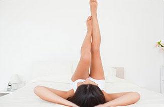 donna distesa a letto con piedi in alto per aumentare la circolazione