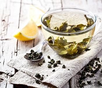 infuso di tè verde con semi di cannella e limone su tovaglia da cucina