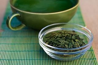 foglie di green tea te verde in ciotola di vetro su tovaglietta verde
