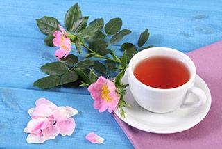 tisana dimagrante di te da erbe mediche in tazza bianca su tovaglia colorata