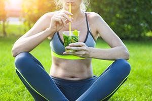 donna che beve tisana dimagrante alle erbe seduta su un prato dopo attività