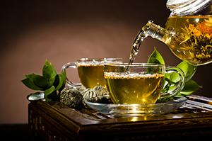 tazza con erbe verdi di tisana dimagrante versata da una teiera