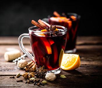 vino caldo in tazza trasparente con fruttas tagliata fresca e cannella
